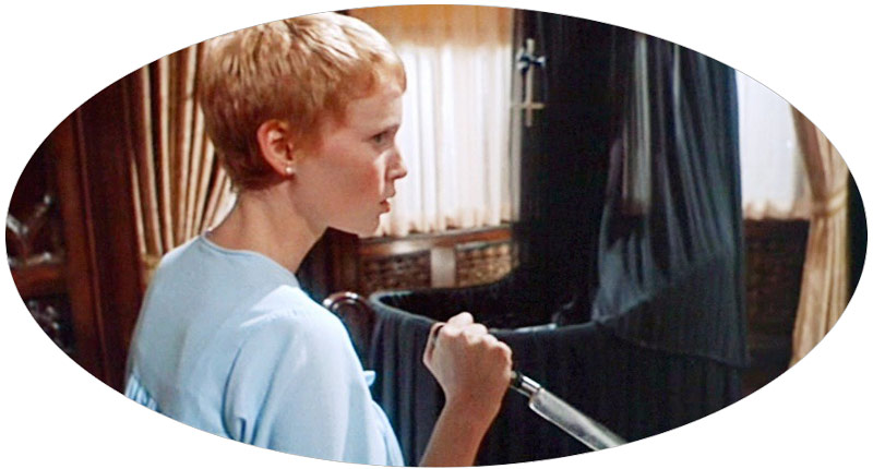 still from the film Rosemary's Baby — we see Mia Farrow handling a sharp knife with a black gothic cradle in the background
