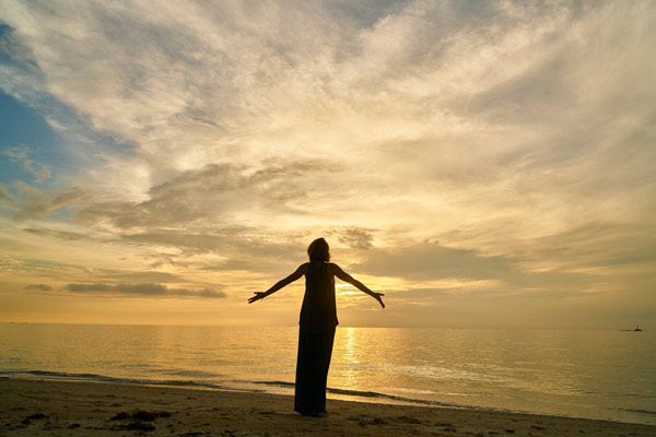 Silhouette of a woman on the beach opening her arms towards the sea and sky. The sky is in the twilight or dawn.